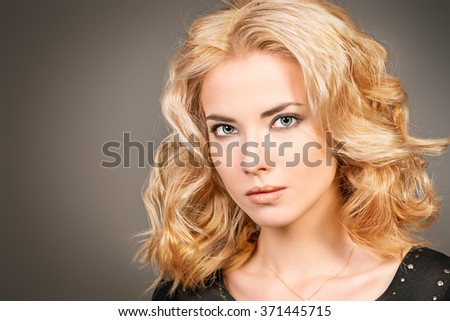 Close-up portrait of a beautiful blonde woman with stunning eyes over gray background.  Beauty, fashion. Make-up, smoky eyes. - stock photo