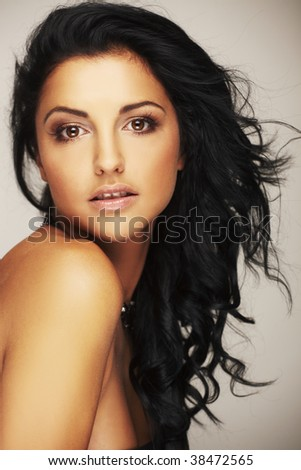 Close-up portrait of a beautiful brunet model in studio on light background - stock photo