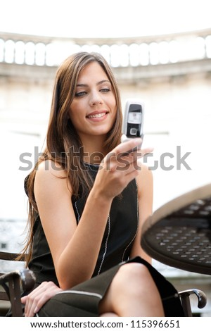 Close up portrait of a beautiful businesswoman using a cell phone while sitting in a classic coffee shop, smiling. - stock photo