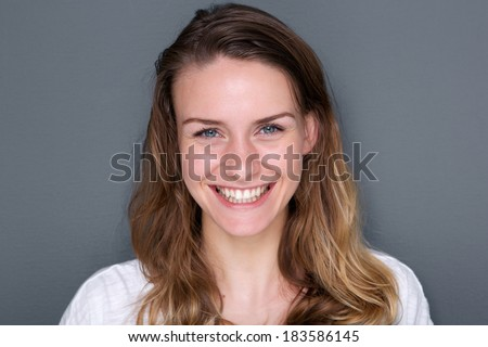 Close up portrait of a beautiful caucasian young woman smiling on gray background - stock photo