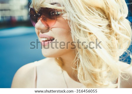close-up portrait of a beautiful charming girl hipster blonde in sunglasses laughing and posing with full lips - stock photo