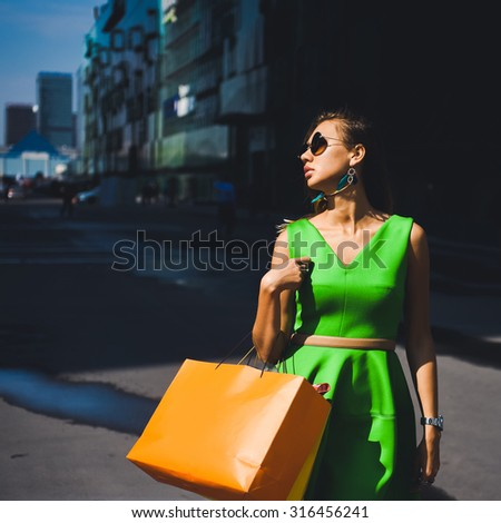 close-up portrait of a beautiful charming girl hipster blonde in sunglasses sexy and posing with full lips in a green dress and earrings with feathers on shopping - stock photo