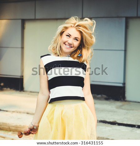 close-up portrait of a beautiful charming girl hipster  blonde with full lips in a striped dress laughing and posing - stock photo