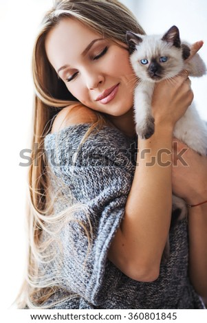 close-up portrait of a beautiful girl holding british cat. Portrait of a beautiful girl in warm sweater. - stock photo