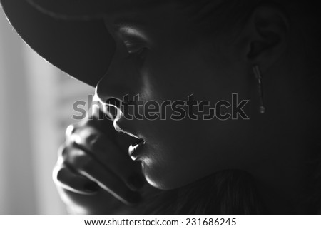 Close-up portrait of a beautiful girl in a fashionable hat, black and white - stock photo