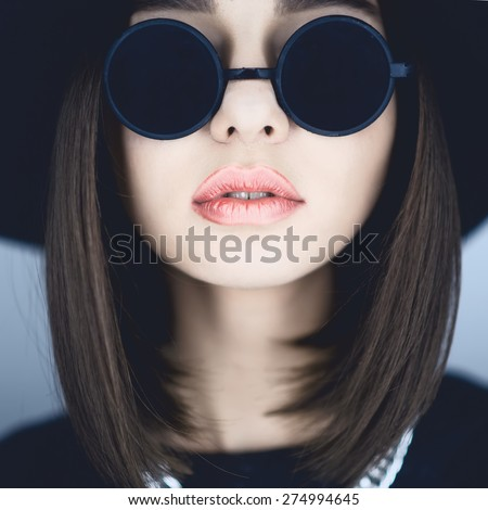 Close-up portrait of a beautiful girl in glasses with red lips - stock photo
