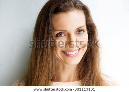 Close up portrait of a beautiful middle aged woman smiling against white background - stock photo