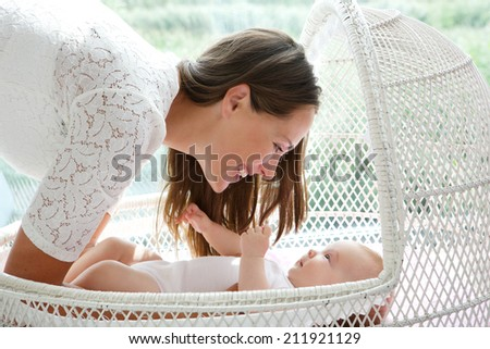close up portrait of a beautiful mother smiling with cute baby - stock photo