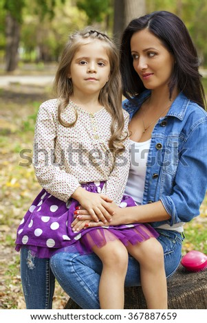 Close up portrait of a beautiful nine year old little girl and happy mother in autumn park - stock photo
