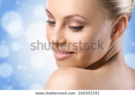 close-up portrait of a beautiful nude woman on blue sky, bokeh and white snowflakes background - stock photo