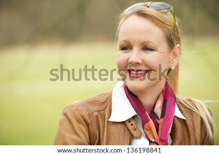 Close up portrait of a beautiful older woman smiling and enjoying life outdoors - stock photo