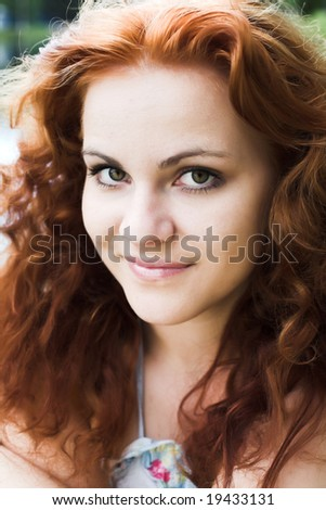 Close-up portrait of a beautiful red-headed girl - stock photo