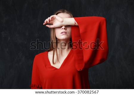 Close up portrait of a beautiful sad woman in red dress,her eyes are closed by the hand, dramatic pose, gray background