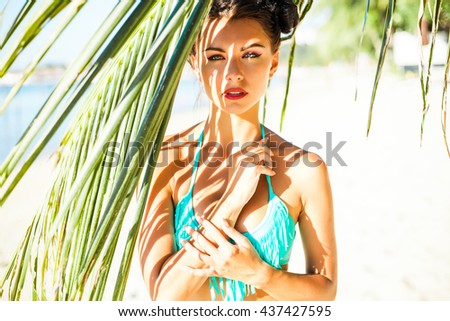 close-up portrait of a beautiful sexy amazing luxurious brunette with blue eyes girl standing under a palm tree on the beach, relaxing on a tropical island, makeup and hairstyle with horns, fashion - stock photo