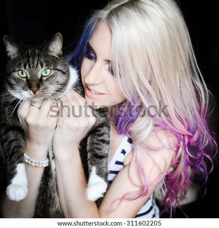 close-up portrait of a beautiful sexy young blonde girl hipster with lilac and pink hair on the background of blooming lilacs, posing and smiling hugging cat  - stock photo
