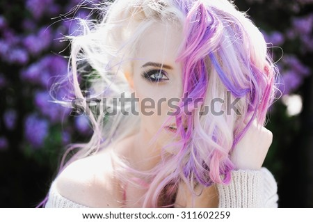 close-up portrait of a beautiful sexy young blonde girl hipster with lilac and pink hair on the background of blooming lilacs, posing - stock photo