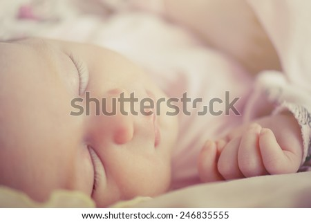 Close-up portrait of a beautiful sleeping baby girl. Cute infant kid. Child portrait in pastel tones. - stock photo