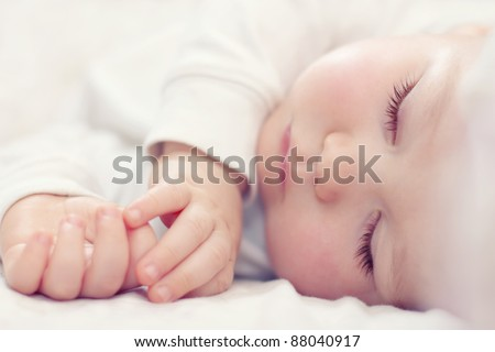 close-up portrait of a beautiful sleeping baby on white - stock photo