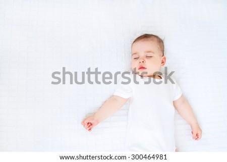 Close-up portrait of a beautiful sleeping baby on white bakcground - stock photo