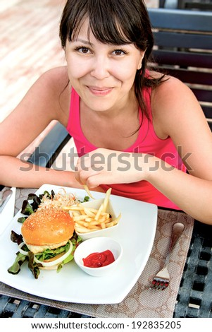 Close up portrait of a beautiful smile young happy asian female eating fresh burger - stock photo