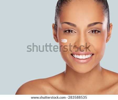 Close-up portrait of a beautiful smiling african woman with cream on her face  - stock photo