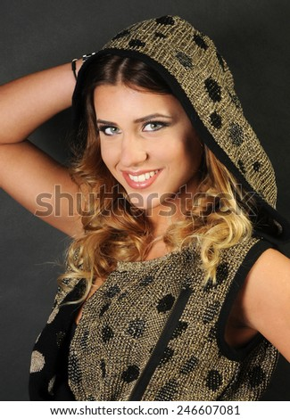 close up portrait of a beautiful smiling caucasian girl with long curly hair wearing Golden vest with black polka dots holding her hand up behind her head - stock photo