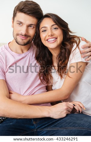 Close-up portrait of a beautiful smiling couple sitting on the couch over white background - stock photo