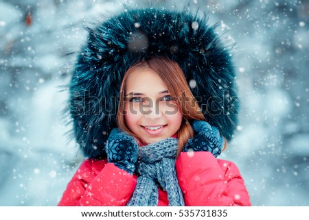 Close up portrait of a beautiful smiling girl in fur hood, knitted scarf, mitten and red clothes having fun outdoor under snowflakes.Pretty young model looking at camera. Warm art photo.