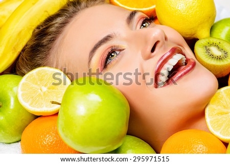 Close-up portrait of a beautiful smiling woman among fresh fruts. Healthy eating, juice. Make-up, cosmetics. Healthy teeth. - stock photo