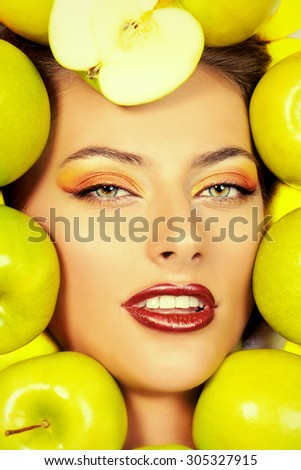 Close-up portrait of a beautiful smiling woman among fresh green apples. Healthy eating concept. Make-up, cosmetics. Healthy teeth. - stock photo