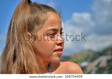 Close up portrait of a beautiful tanned teenager girl by the swimming pool - stock photo