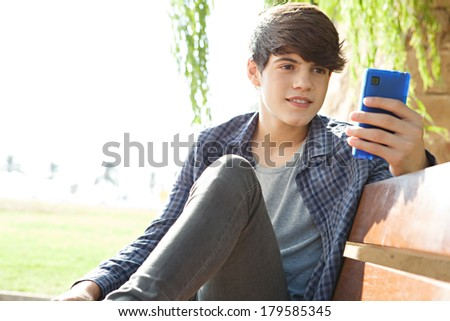 Close up portrait of a beautiful teenager boy sitting and relaxing on a wooden park bench, holding and using his smartphone device to network and browse on-line. Technology lifestyle. - stock photo