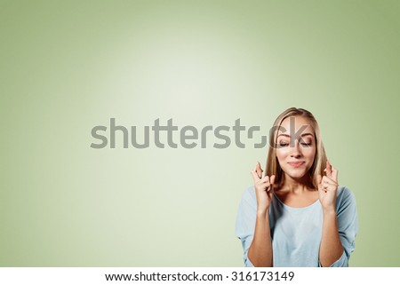 Close-up portrait of a beautiful woman closing her eyes, crossing her fingers hoping for the best,isolated on green background - stock photo