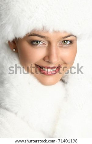Close-up portrait of a beautiful woman in white fur cap - stock photo