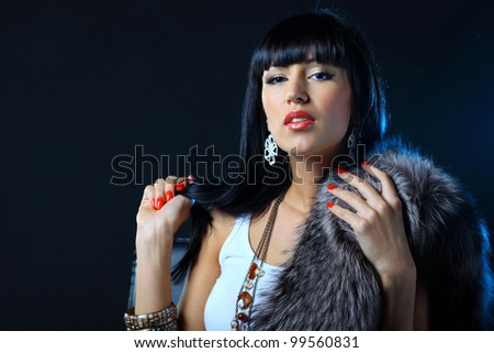 Close-up portrait of a beautiful woman isolated on dark background - stock photo