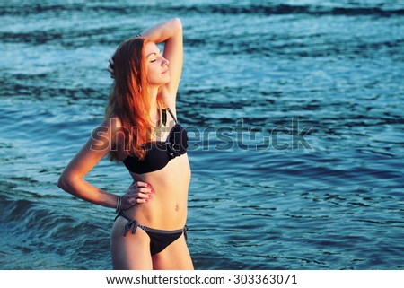 Close-up portrait of a beautiful woman on the beach at sunset relaxation and having fun in the summer break. - stock photo