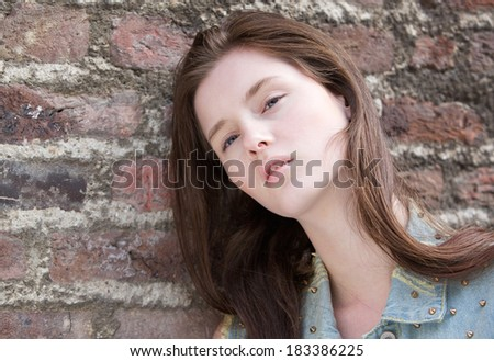 Close up portrait of a beautiful woman posing against brick wall outdoors