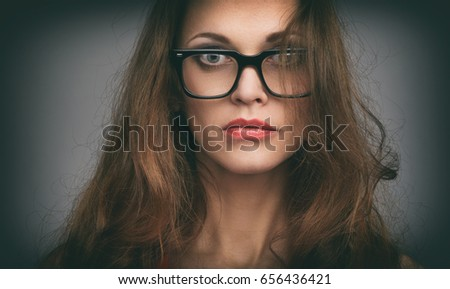 Close up portrait of a beautiful woman wearing glasses. Girl looking seriously at camera