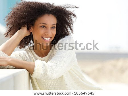 Close up portrait of a beautiful young african american woman relaxing outdoors - stock photo