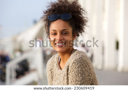 Close up portrait of a beautiful young african american woman smiling outdoors - stock photo