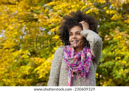 Close up portrait of a beautiful young african american woman smiling with hand in hair - stock photo