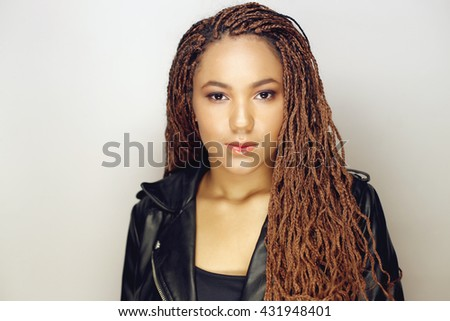Close up portrait of a beautiful young african american woman wearing black leather jacket - stock photo