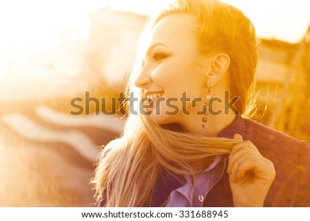 close-up portrait of a beautiful young blonde girl in stylish  autumn with dark red full lips smiling at sunset on a sunny day and posing lifestyle in the city
