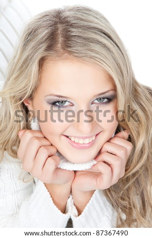 Close-up portrait of a beautiful young blonde woman  in white sweater lying on the sofa on white background