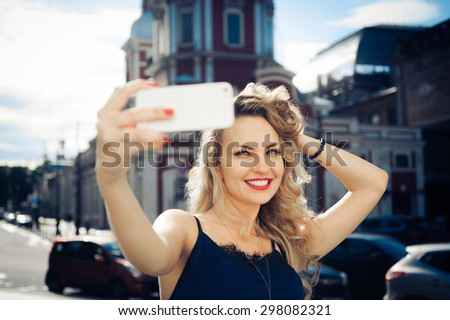 close-up portrait of a beautiful young blonde woman  with red lips with curly hair with the phone in hand, laughing and posing and makes selfi