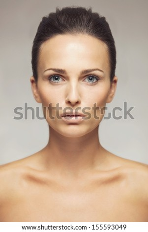 Close-up portrait of a beautiful young brunette with grey eyes looking at camera. Pretty woman with clean and glowing skin isolated on gray background - stock photo