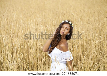 Close up portrait of a beautiful young brunette woman in a wheat field - stock photo