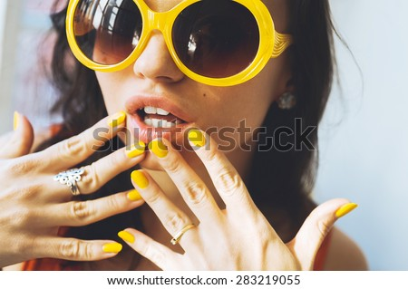 close-up portrait of a beautiful young brunette woman with full lips in yellow retro sunglasses and yellow varnish on the nails, posing and smiling for the camera - stock photo