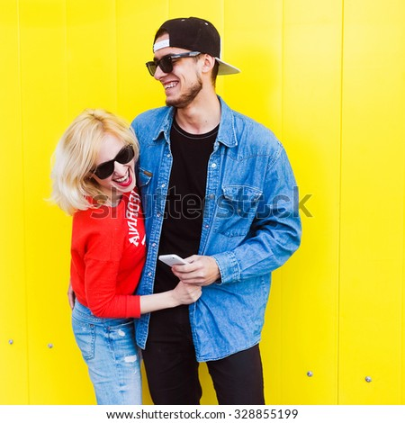 close-up portrait of a beautiful young couple in love bright blonde girl with red lips and a guy with a beard wearing a cap hipsters  yellow background smiling and posing lifestyle  telephone selfie - stock photo
