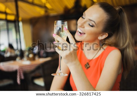 close-up portrait of a beautiful young elegant sexy blonde woman in the cafe with a glass of champagne,White wine  smiling  and drink posing, with a ring on her finger, she is engaged - stock photo